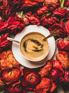 Black espresso coffee in cup on red ranunculus flower background