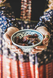 Woman in oriental dress holding bowl of dates for Ramazan