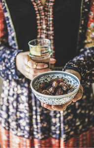 Woman holding dates and water for Ramazan Iftar meal