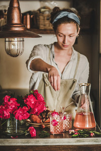 Young woman adding ingredients to glasses with rose lemonade