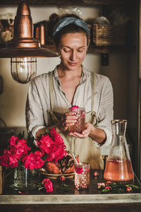 Young woman holding glass of rose homemade lemonade in hands