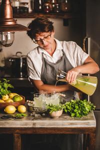 Elderly woman making fresh homemade lemonade in kitchen