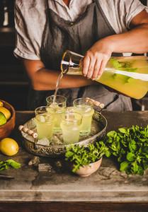 Hands of woman making fresh homemade lemonade over kitchen counter