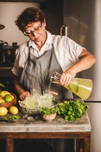 Elderly woman making fresh homemade lemonade over kitchen counter
