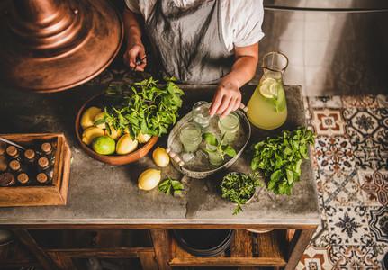 Woman adding fresh mint to homemade citrus lemonade