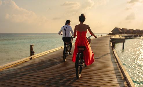 Couple cycling at a tropical sea resort