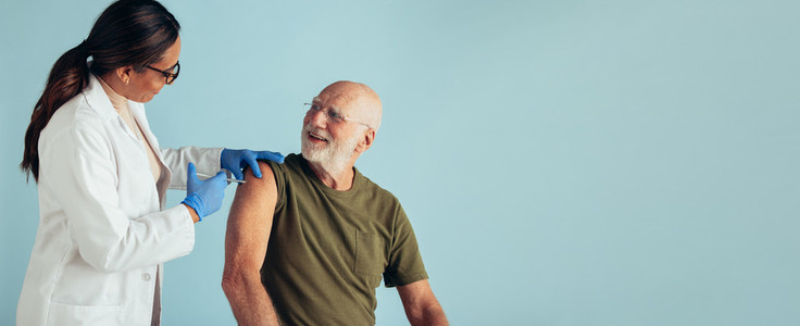Senior man getting vaccinated on blue background