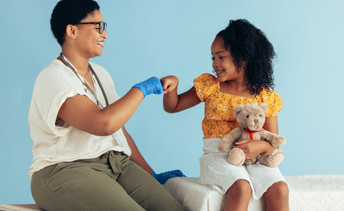 Doctor giving fist bump to girl patient