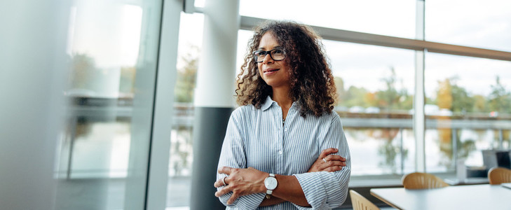Woman entrepreneur standing at office window