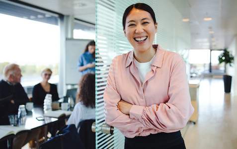 Cheerful female professional outside boardroom