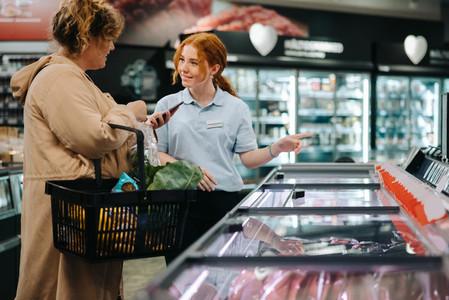 Saleswoman assisting shopper in supermarket