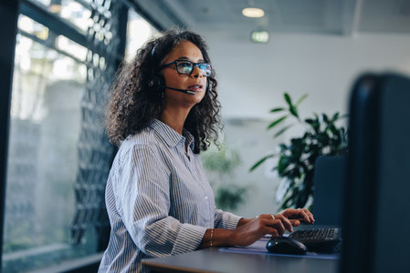 Businesswoman with headset working on computer