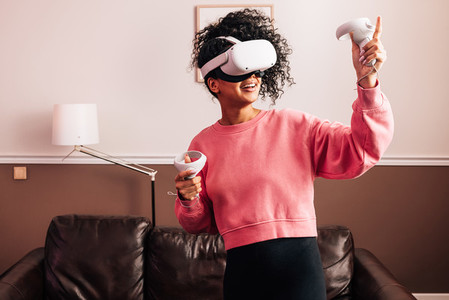 Young woman having fun with VR set  Smiling female using a virtual reality headset