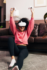 Happy woman in casual clothes raise hands up holding joysticks from VR set