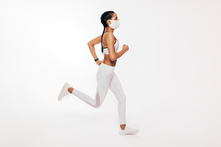 Side view of young fitness woman running over white background wearing a face mask