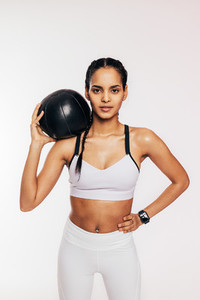 Portrait of a muscular fitness woman with a medicine ball on her shoulder