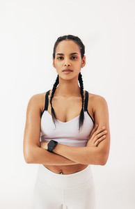 Confident fitness woman with braids standing in studio and looking at camera