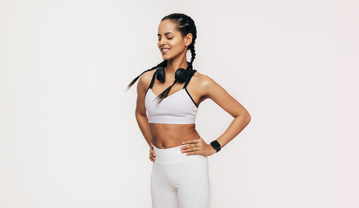 Smiling sportswoman with closed eyes standing in studio with hands on hips