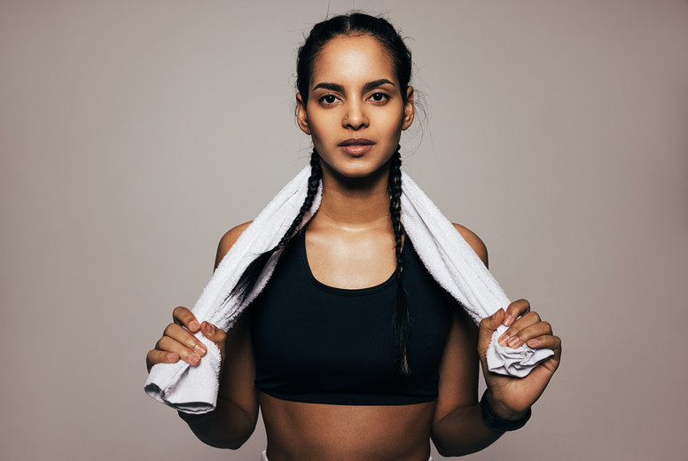 Close up portrait of a mixed race woman in sportswear holding a white towel