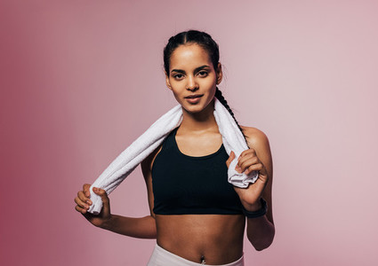 Portrait of a young sportswoman posing in studio with white towel