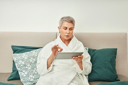 Mature woman with grey hair using a digital tablet in bedroom