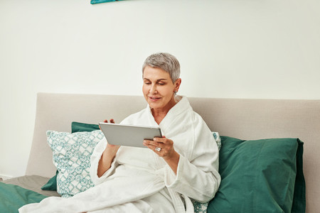 Smiling mature woman in bathrobe relaxing on a bed holding a digital tablet