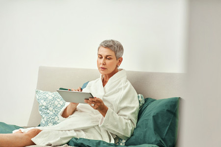 Mature woman relaxing at home  Senior female making online order while lying on a bed