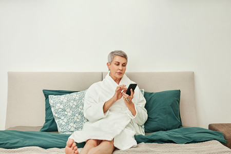 Senior woman typing on her smartphone lying on a bed
