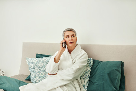 Mature woman wearing bathrobe making phone call from bedroom