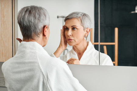 Senior female touching her face in a bathroom  Mature woman inspecting face in the morning