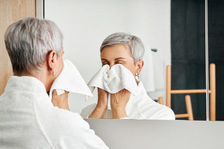 Senior woman wiping face with towel while standing in front of a mirror