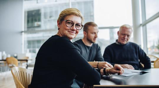 Happy senior businesswoman in boardroom meeting