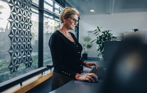 Senior businesswoman working at standing desk in office