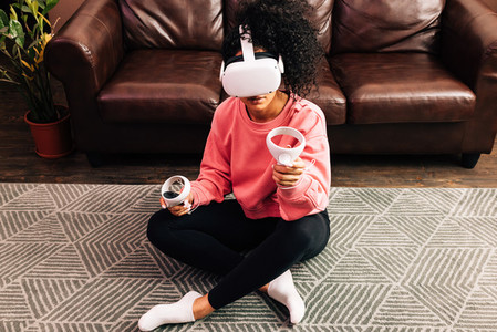 Young woman in casual clothes sitting on the floor in living room using VR set