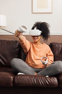 Young cheerful woman relaxing at home using virtual reality headset on couch