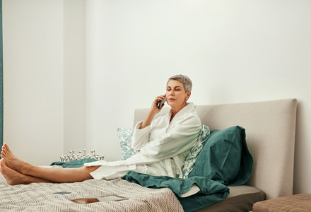 Mature woman talking by phone lying on her bed after home spa