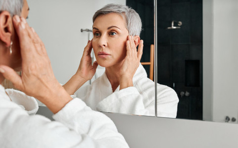 Mature woman in bathrobe looking herself in the bathroom mirror