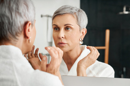 Senior woman with moisturizer on her face looking at mirror in bathroom
