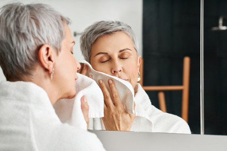 Mature woman with short grey hair using a towel after washing up face