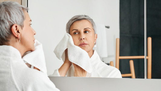 Beautiful mature woman doing morning routine in bathroom wiping the face