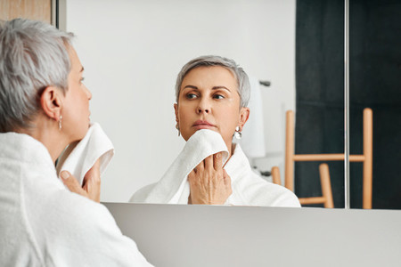 Mature woman standing in front of a mirror wiping her chin with towel
