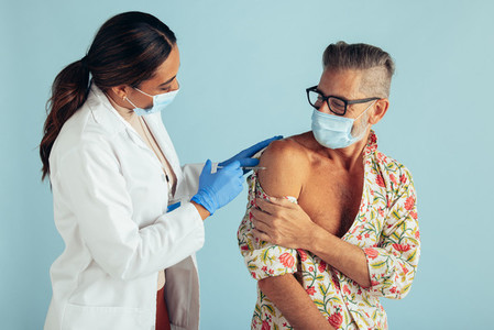 Doctor giving corona virus vaccine to mature man