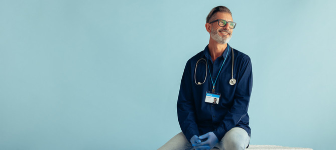 Mature doctor on blue background