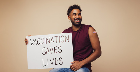 Man holding Vaccination saves lives placard