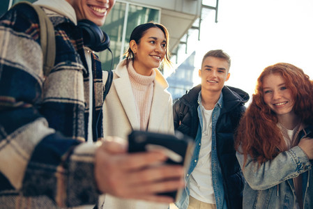 Students looking at cell phone and smiling