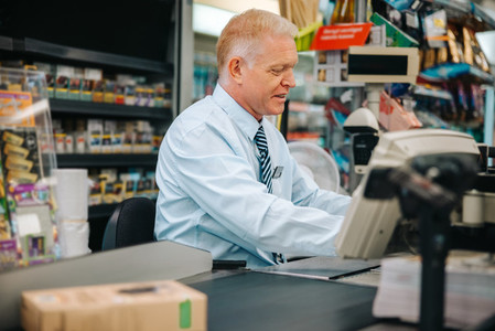 Senior cashier working at grocery store