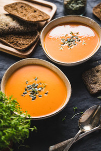 Vegetable creamy healthy soup with pumpkin seeds on a kitchen table