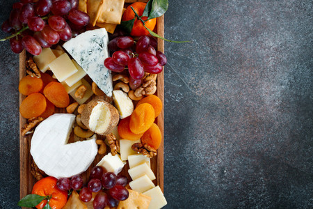 Big cheese board with appetizer assortment  Grape  cheese  nuts  jam and bread