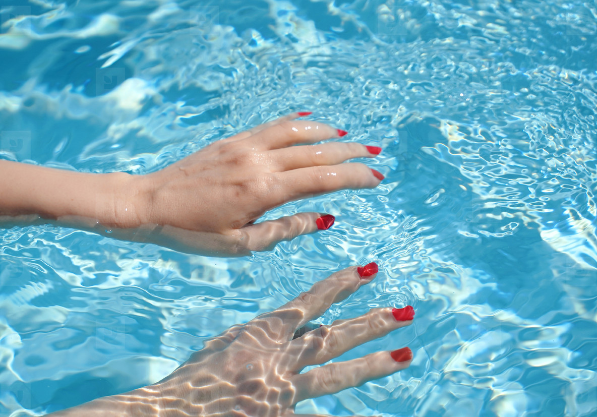 Close up of woman hands with manicure in red under clear pool wa