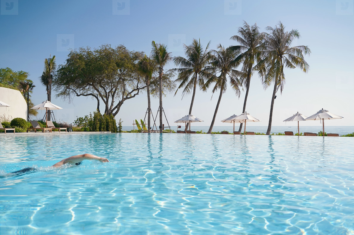 Tourist swimming in the luxury pool resort with seaside view  su